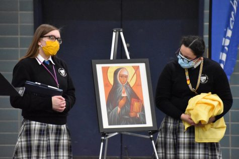 Junior Abby Wojtaszek and sophomore Sophia Mendez present the biography of Saint Katharina Kasper, the founder of the Poor Handmaids of Jesus Christ