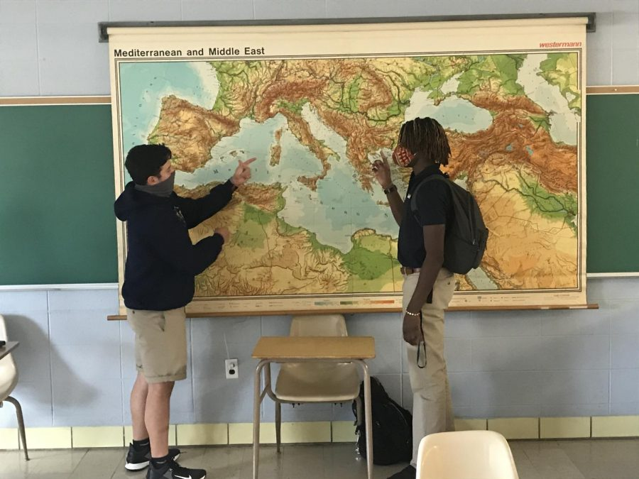 Students Ethan Lopez and Kayode Olaoye talking over geography and history.
