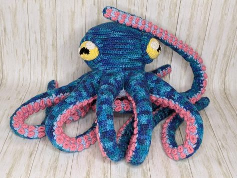 Blue octopus with pink suction cups and yellow eyes, entirely crocheted.